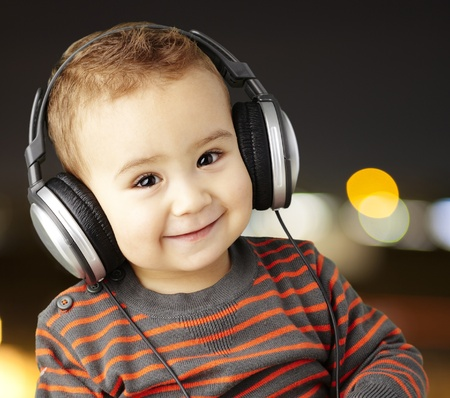 innocent: young boy wearing headphones and smiling against a city by night