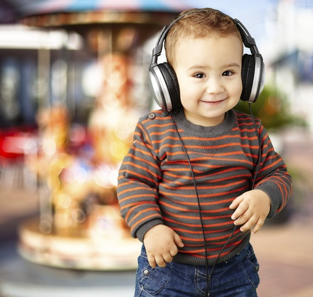 young boy wearing headphones and smiling against a carousel background photo