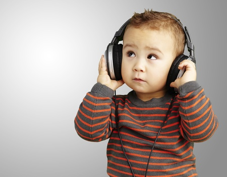 young boy wearing headphones and looking up against a grey background photo