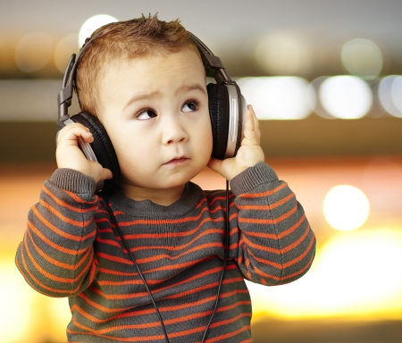 listen: young boy wearing headphones and looking up against a city by night