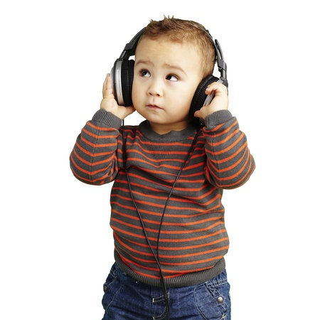 young boy wearing headphones and looking up against a white background photo