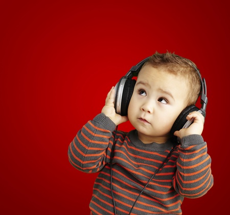 playing music: young boy wearing headphones and looking up against a red background Stock Photo