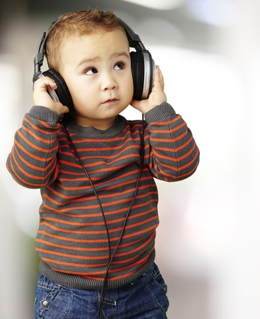earbud: young boy wearing headphones and looking up, indoor