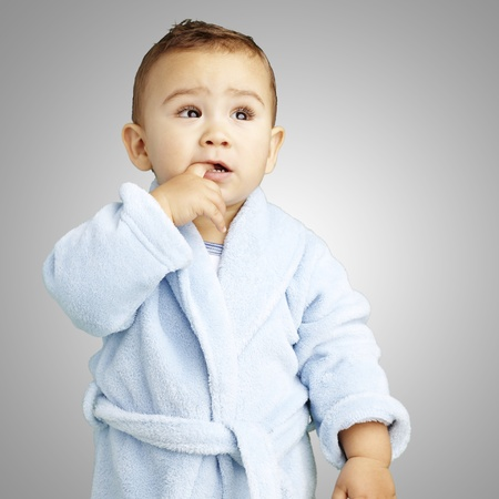young boy wearing a bathrobe with his finger in his mouth against a grey background photo