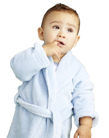 young boy wearing a bathrobe with his finger in his mouth against a white background photo