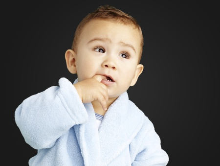 young boy wearing a bathrobe with his finger in his mouth against a black background Stock Photo - 13486183