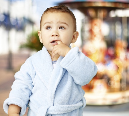 young boy wearing a bathrobe with his finger in his mouth against a carousel background  photo