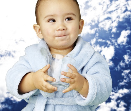 young boy wearing a bathrobe and holding a glass against a cloudy sky background photo
