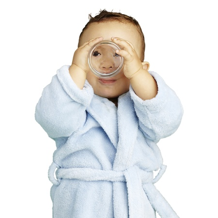 young boy wearing a bathrobe and drinking against a white background photo