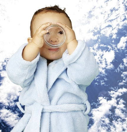 young boy wearing a bathrobe and drinking against a cloudy sky background photo