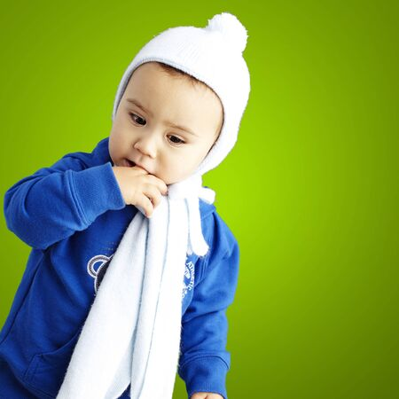 young boy with his finger in his mouth thinking against a green background