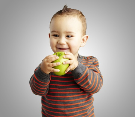 happy boy holding a green apple against a grey background