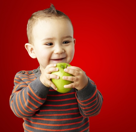 happy boy holding a green apple against a red background photo