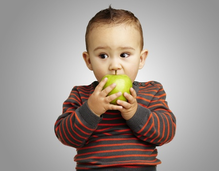 hungry kid: young boy eating a green apple against a grey background Stock Photo