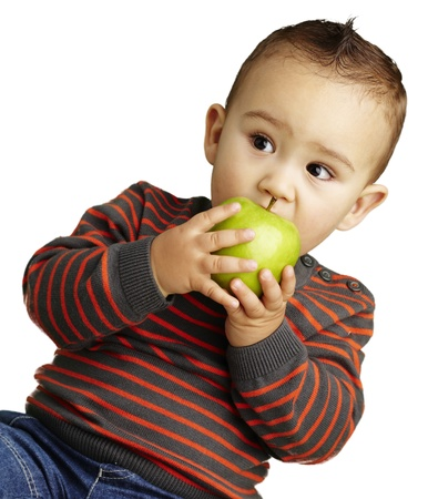 young boy eating a green apple against a white background photo