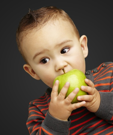 young boy eating a green apple against a black background photo