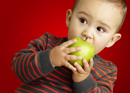 young boy eating a green apple against a red background photo