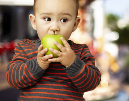 young boy eating a green apple against a carousel background photo
