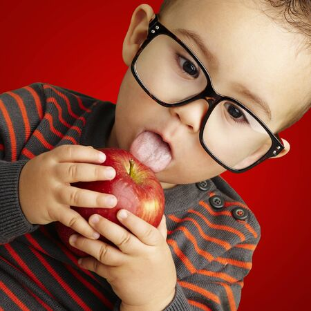 young boy licking a red apple against a red background photo