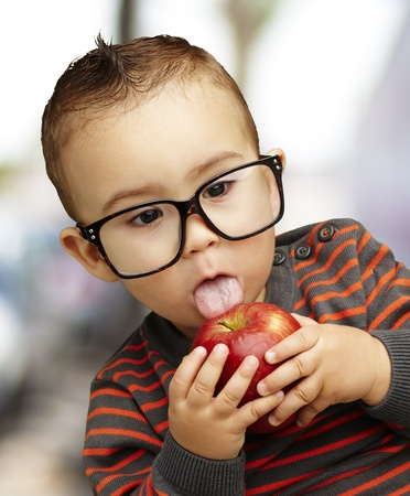 young boy eating a red apple, indoor Stock Photo - 13486380