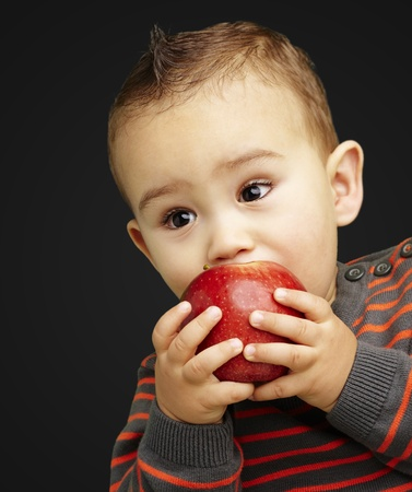 young boy eating a red apple against a black background Stock Photo - 13486359