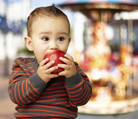 young boy eating a red apple against a carousel background photo