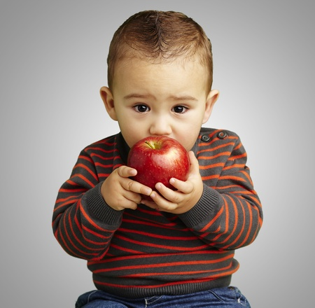 young boy tasting a red apple against a grey background photo