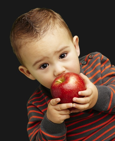 young boy tasting a red apple against a black background photo