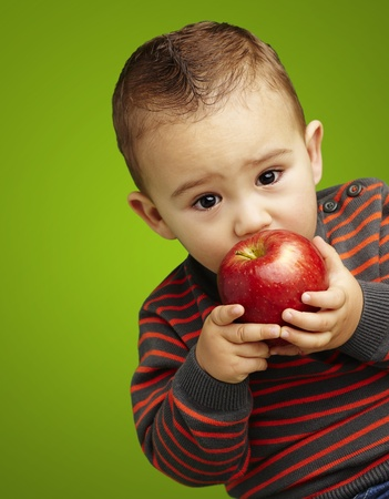 young boy tasting a red apple against a green background Stock Photo