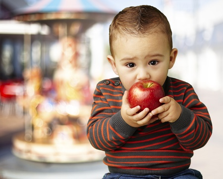 young boy tasting a red apple against a carousel background photo