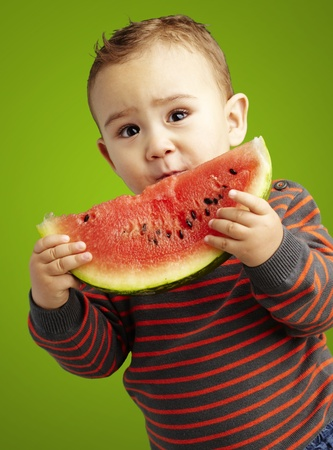 sweet boy holding a watermelon slice against a green background photo