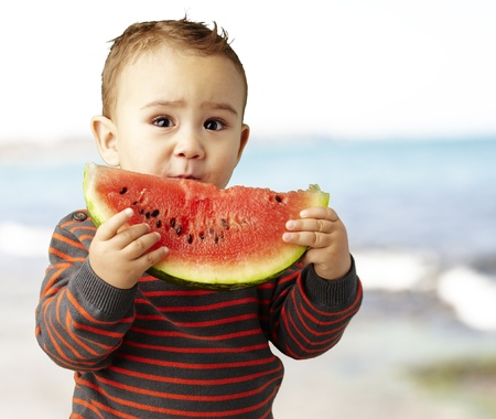 sweet boy holding a watermelon slice, outdoor photo