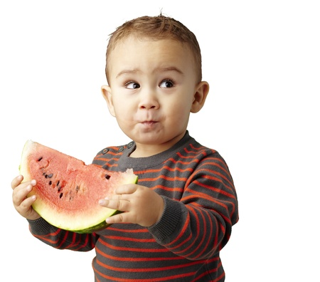 sweet boy holding a watermelon slice and looking up against a white background Stock Photo - 13486366