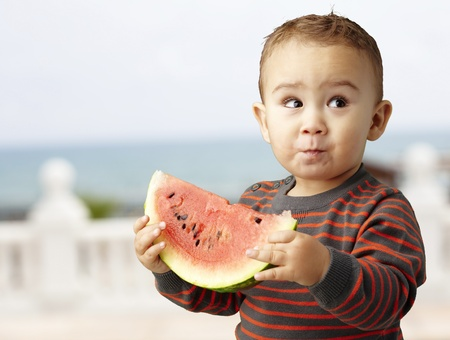 sweet boy holding a watermelon slice and looking up, outdoor photo