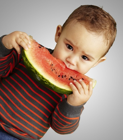 boy eating a watermelon slice and looking forward against a grey background photo