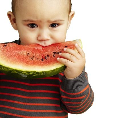 niño de comer una rebanada de sandía y con ganas contra un fondo blanco Foto de archivo - 13486376