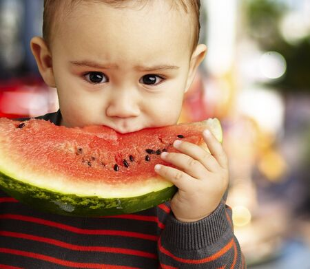 health fair: boy eating a watermelon slice and looking forward, outdoor
