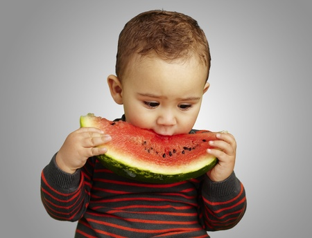 kids eating healthy: boy eating a watermelon slice against a grey background