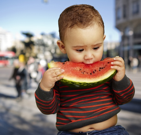 boy eating a watermelon slice against a street background photo