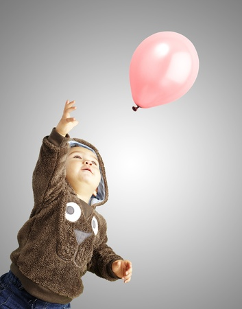 young boy trying to catch a pink balloon against a grey background photo