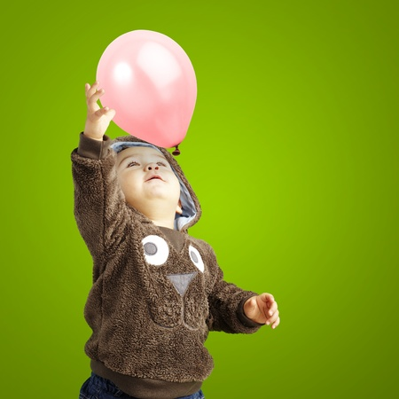 young boy trying to catch a pink balloon against a green background photo