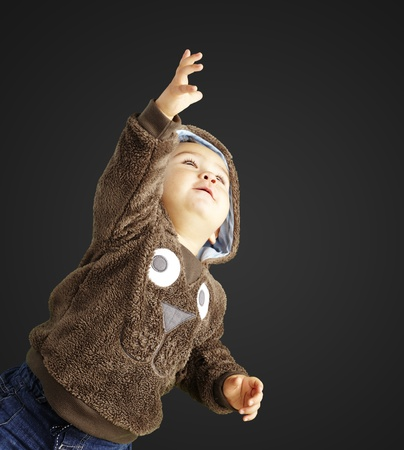 young boy pointing up against a black background photo