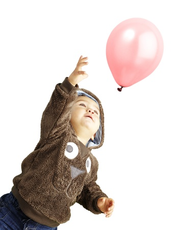 young boy trying to catch a pink balloon against a white background photo