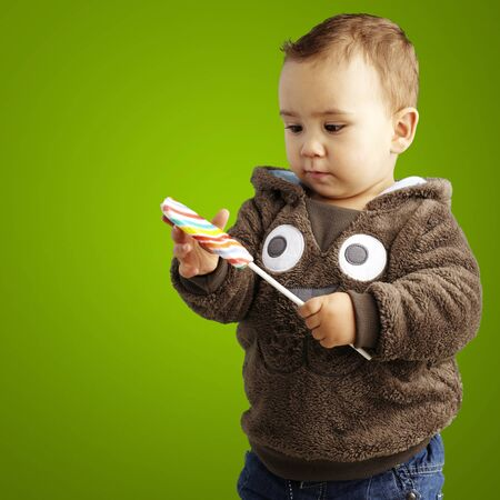 young boy holding a candy bar against a green background photo