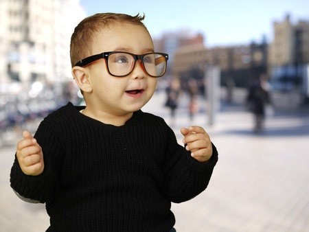 young boy wearing glasses and laughing against a street background photo
