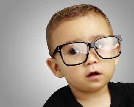 funny glasses: young boy wearing glasses and looking up against a grey background