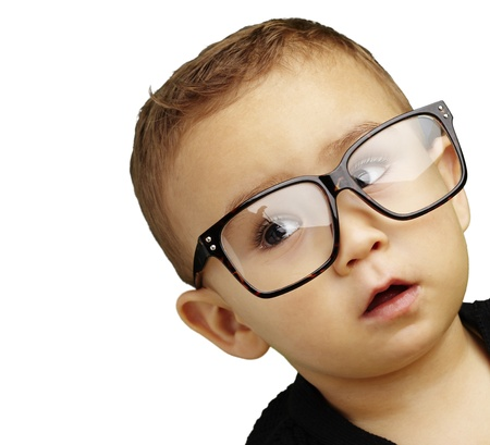 young boy wearing glasses and looking up against a white background Stock Photo