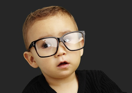 enthusiastic: young boy wearing glasses and looking up against a black background Stock Photo