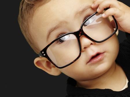 glass eye: chico joven con gafas y mirando hacia arriba contra un fondo negro Foto de archivo