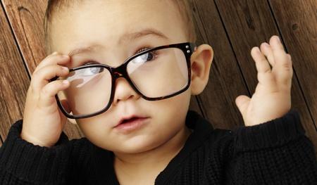 ni�os pensando: chico joven con gafas y mirando hacia arriba contra un fondo de madera Foto de archivo